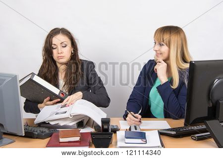 The Situation In The Office - One Employee Overburdened, The Other Does Nothing And Laughs Looking A
