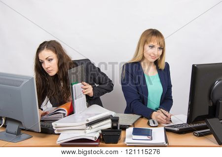 Colleagues In The Office Girls, Both Looking To The First Monitor With A Bunch Of Papers And Folders