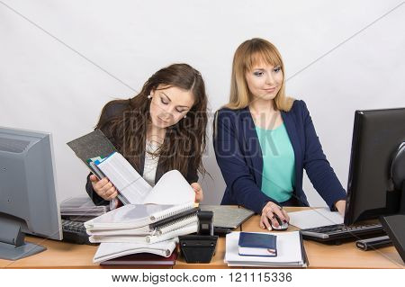 Female Colleagues In The Office, One Works With Paper Documents, The Second Computer With Electronic