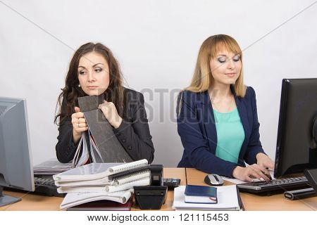 Female Colleagues In The Office, A Tired Looking In The Monitor, The Other Happy Working On A Comput