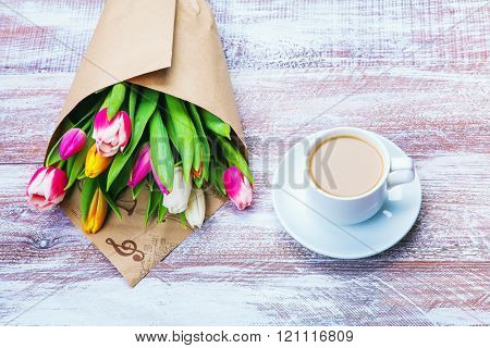 the bouquet of tulips is wrapped in a paper isolated on a wood background