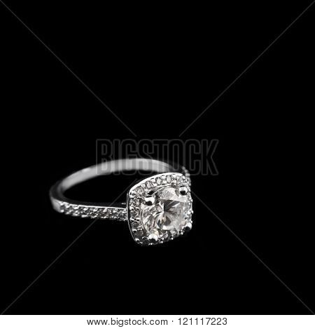 Luxury jewellery. White gold or silver engagement ring with diamonds closeup on black background. Se