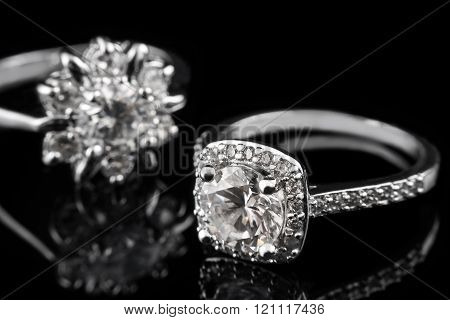 Luxury jewellery. White gold or silver engagement rings with diamonds closeup on black glass backgro