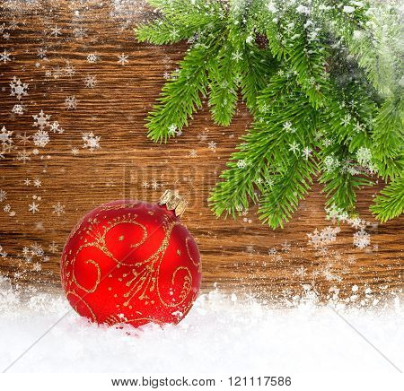 Red Christmas Ball On Snow With Spruce Twigs On Wooden Background