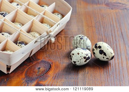 Quail eggs in wooden box packaging tray on wooden background