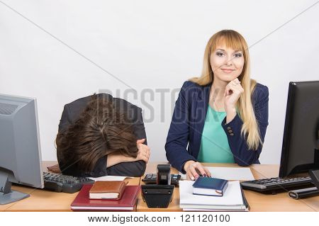 The Situation In Office - Frustrated Woman Lay On The Table, Her Colleague Happily Looks Into The Fr