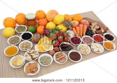 Health food and natural herbal medicine selection for cold and flu remedy including foods high in antioxidants and vitamin c on bamboo over white background.