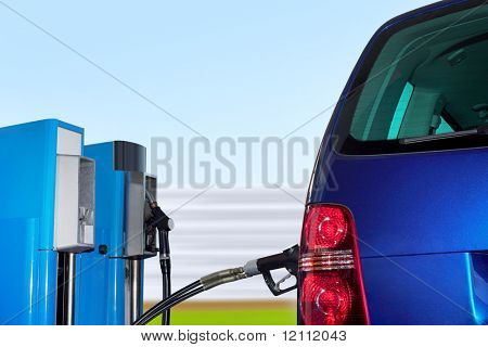 At the gas station pump putting gas into the car