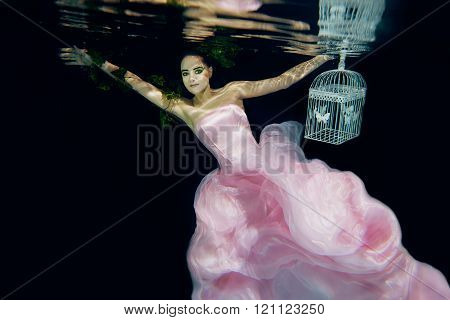 young beautiful girl in long red dress with cage in her arms underwater