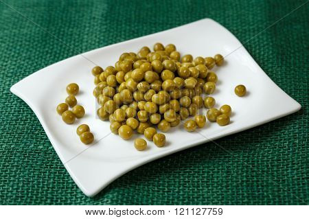 Green peas on a white plate on green background