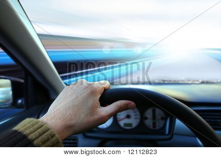 hand of driver that holds wheel and goes on road