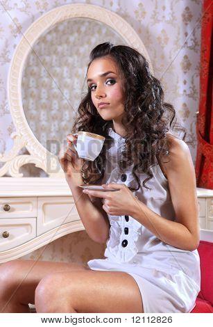 sad young woman sitting on armchair drinking tea