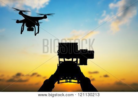 Man hands handling drone in sunset silhouettes