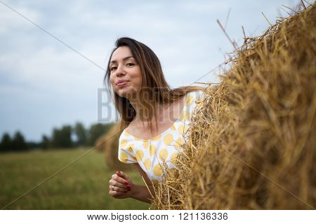 she coyly peeping from behind a haystack