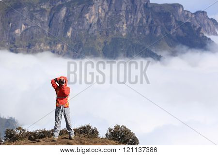 young woman hiker taking photo on mountain peak