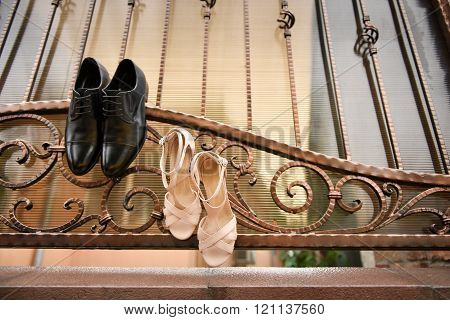 Groom Black Shoes And White Shoes Hanging In A Wrought Iron Fence