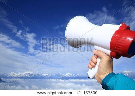 hand hold loudspeaker to blue sky on mountain peak