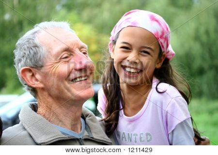 A Young Girl Sharing A Joke With Her Grandfather