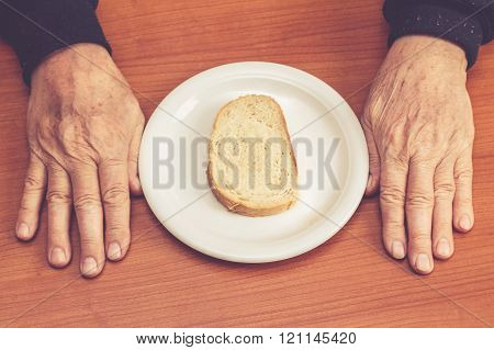 Old Man's Hands On Table With One Slice Of Bread In Middle