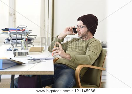 corporate portrait of young happy hipster businessman working from modern home office as freelancer wearing casual beanie talking on mobile phone in creative freestyle business people