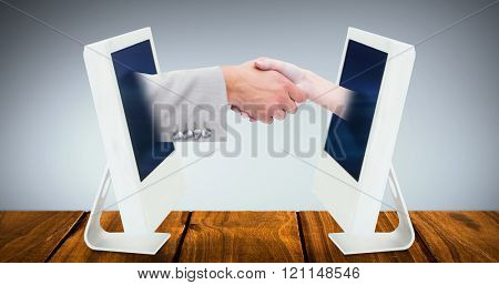 Close up of female and male hand shaking against grey vignette