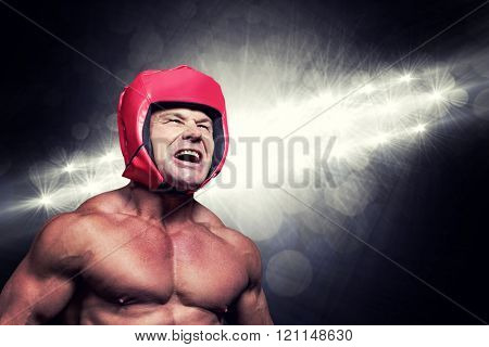 Angry boxer with headgear against spotlights