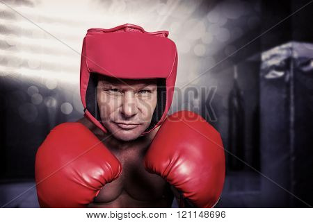 Portrait of boxer with gloves and headgear against red boxing area with punching bags