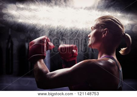 Side view of female boxer with fighting stance against red boxing area with punching bags