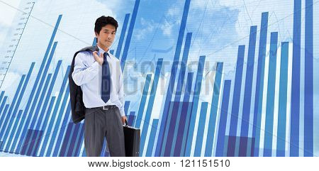 Portrait of a businessman holding a briefcase and his jacket on his shoulder against blue data