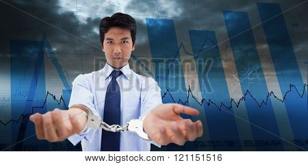 Businessman with handcuffs against blue data