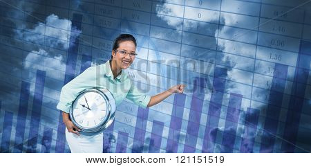 Delighted businesswoman holding a clock against blue data