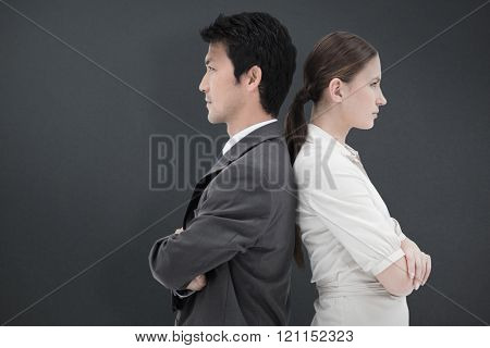 Portrait of serious business people standing back-to-back against grey background