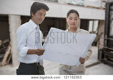 Estate agent and buyer looking at blueprint against workshop