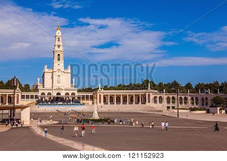 Catholic Cathedral and colonnade in Fatima, Portugal. Believers and tourists walk on the square in front of the cathedral