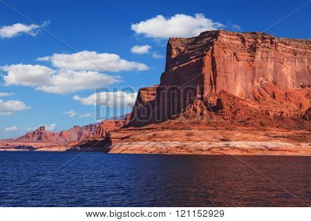 Lake Powell is surrounded by magnificent red hills. Scenic huge artificial water basin of the Colorado River, USA. Walk on the boat at sunset