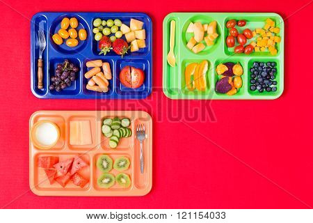 Three Kids Lunch Trays With Fruit
