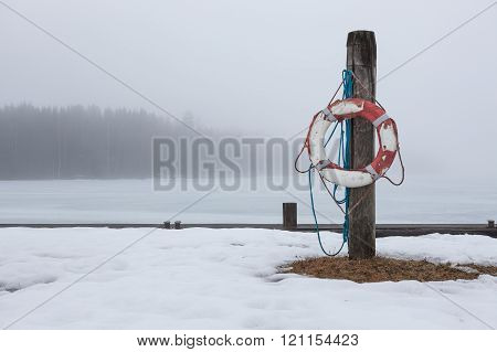 Worn-out lifesaver on post at foggy lake scape