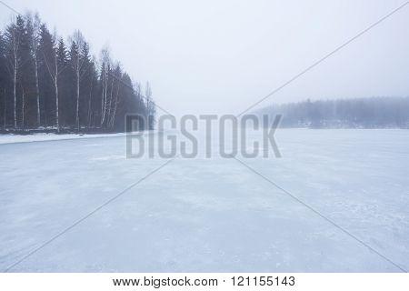 Thick fog at frozen lake landscape