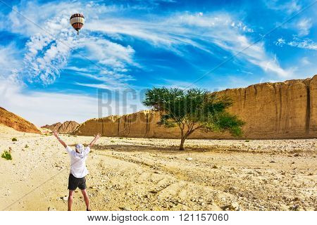 The huge multi-colored balloon flies over desert  near the seaside resort of Eilat. The tourist in white t-shirt is delighted with desert