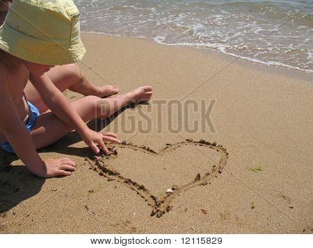 child draw heart on sand
