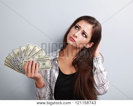 Serious Woman Holding Dollars, Looking Up And Thinking How Little Money She Have Earned And How She