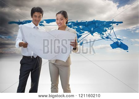 Estate agent looking at blueprint with potential buyer against view of a global map