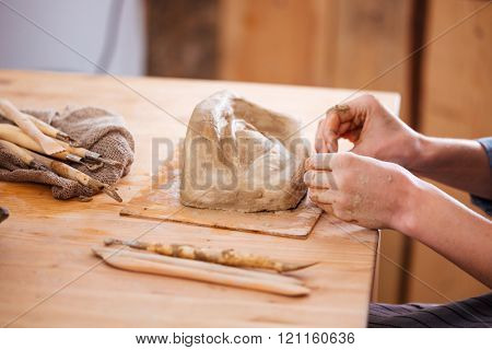 Closeup of hands of young woman ceramist working and finishing sculpture with clay on wooden table in workshop