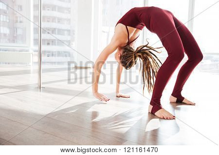 Beautiful young woman with dreadlocks bending and doing yoga in studio