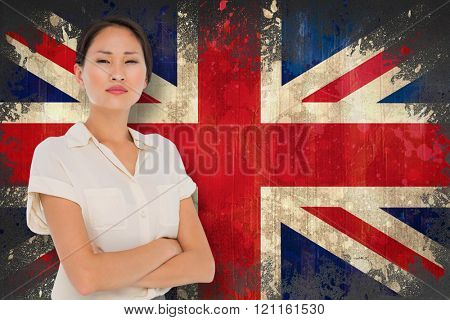 Business colleagues with arms crossed in office against union jack flag in grunge effect