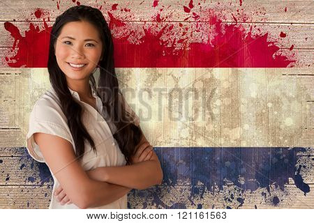 Casual businesswoman looking at camera with arms crossed against netherlands flag in grunge effect