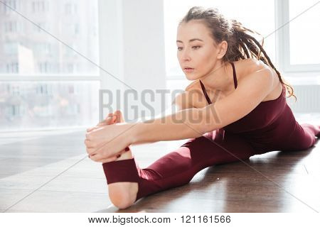 Focused young woman with dreadlocks sitting and stretching legs in front of the window