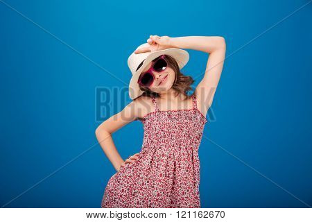 Charming smiling little girl in hat, sundress and sunglasses standing and showing peace sign over blue background