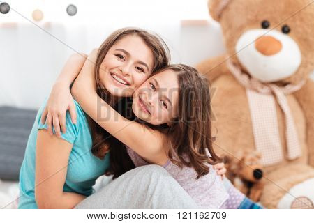Two cheerful charming sisters smiling and embracing at home