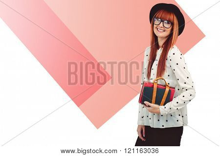 Smiling hipster woman holding book belt against colored background